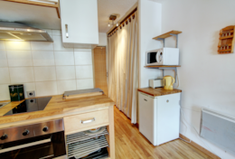 Kitchenette close-up  with stand alone-fridge and microwave.
