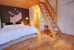 Double bed on the mid-level and stairs leading to the top level of the apartment.
