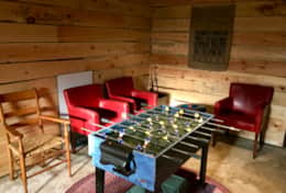 Basement room with 4 single beds, wood pellet stove, and games area