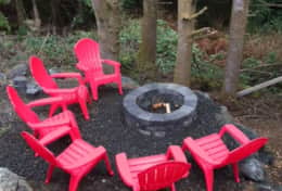 Seating for six at the firepit area looks out onto a lovely forest view.