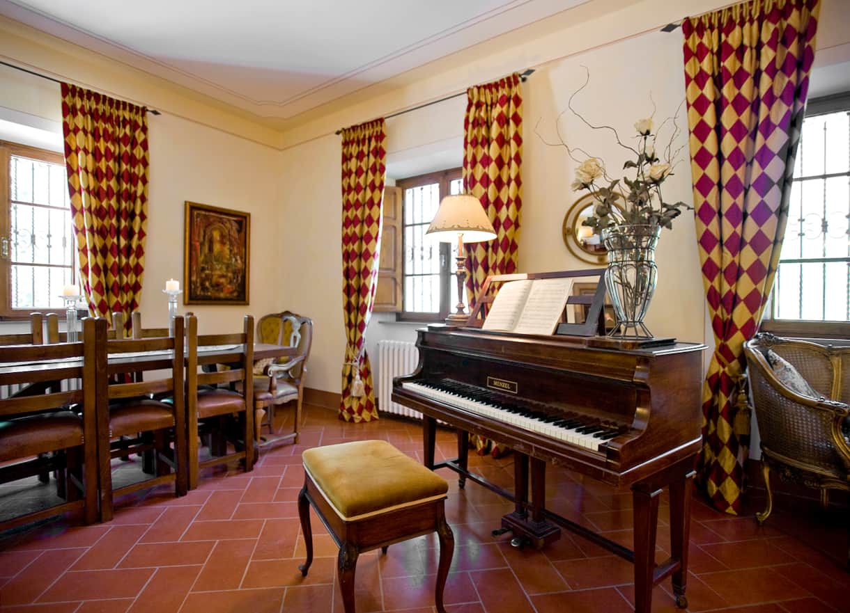 The baby grand piano and  solid walnut Tuscan dining table in this Cortona villa