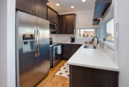 The sleek kitchen in Unit 2 has stainless steel appliances and sleek quartz countertops.