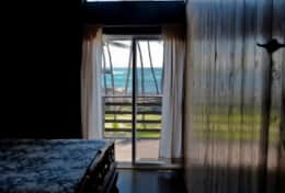 View in the master bedroom looking out towards the beach with private entrance to the lanai.